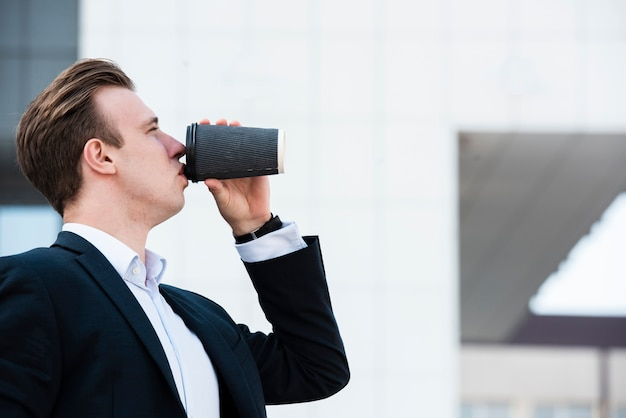 Zijaanzichtzakenman het drinken koffie
