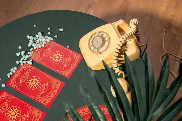 Zijdelings gele telefoon naast rode tarotkaarten