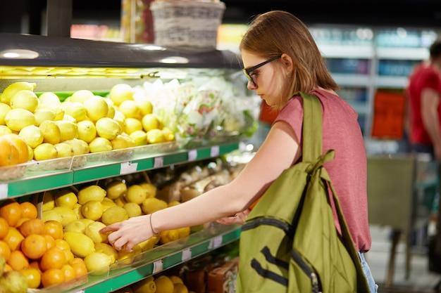 Zijdelings geschoten van mooie jonge vrouw met zak, kiest fruit in kruidenier `s winkel, raakt aan citroenen, doet aankopen in supermarkt, eet gezond voedsel. mensen, consumentisme en koopconcept.