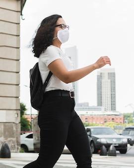 Zijdelings jonge vrouw die in openlucht een medisch masker draagt