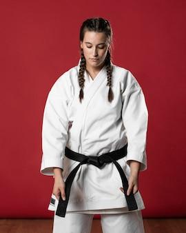 Zijdelings karatevrouw in traditionele witte kimono op rode achtergrond