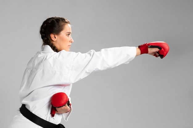 Zijdelings karatevrouw in traditionele witte kimono op witte achtergrond