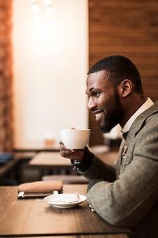 Zijdelings knappe mens die een kop met koffie houdt
