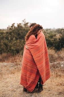 Zijdelings knuffelend paar in deken gewikkeld