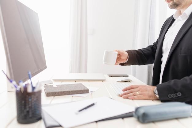Zijdelings man met een kopje koffie aan zijn bureau
