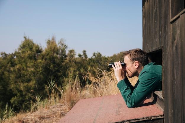 Zijdelings man vogels kijken