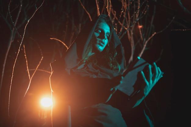 Zijdelings mens die een lantaarn en een boek in de nacht houdt