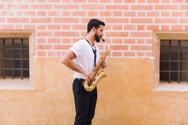Zijdelings middelgroot geschotene mens die de saxofoon speelt