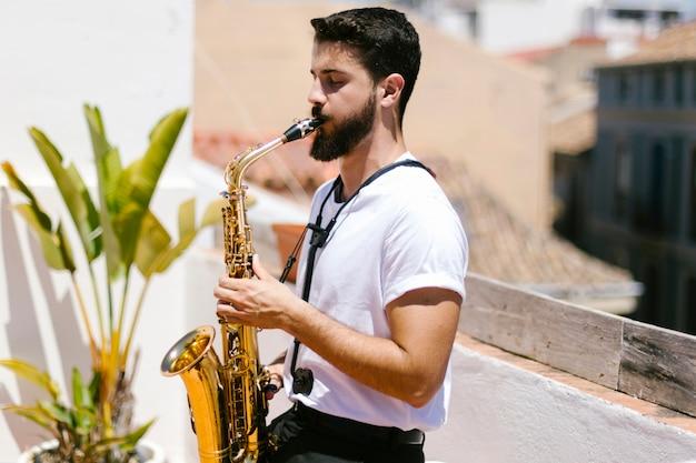 Zijdelings middelgroot schot van de mens die de saxofoon speelt