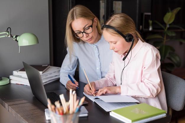 Zijdelings moeder en dochter die aan een online klasse deelnemen