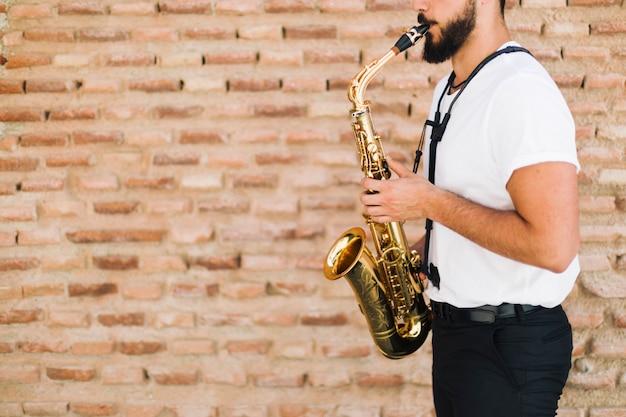 Zijdelings musicus die de saxofoon met bakstenen muurachtergrond spelen