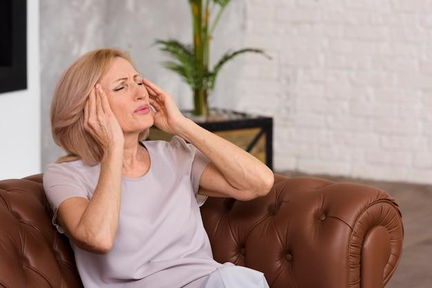 Zijdelings oude dame met hoofdpijn