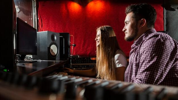 Zijdelings paar dat de schermen in studio bekijkt