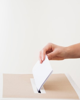 Zijdelings persoon die stemming in verkiezingsdoos zet