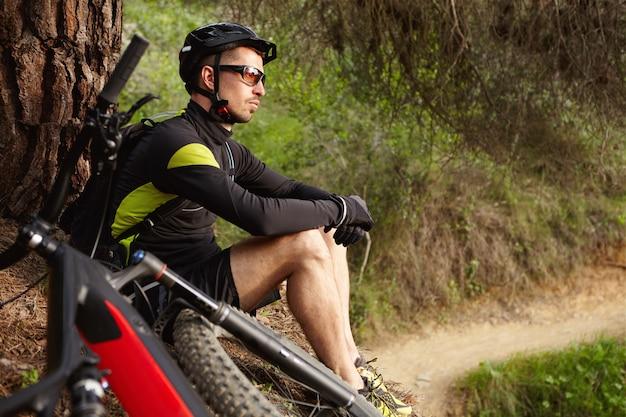 Zijdelings schot van aantrekkelijke gelukkige jonge europese fietser in beschermende uitrusting zittend onder boom met zijn tweewielige motoraangedreven voertuig en overweegt verbazingwekkende wilde natuur om hem heen