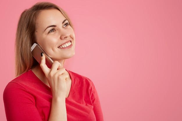 Zijdelings schot van aantrekkelijke gelukkige vrouw heeft een dromerige uitdrukking, praat via een mobiele telefoon, geniet van een gesprek met een vriend, draagt een rode trui