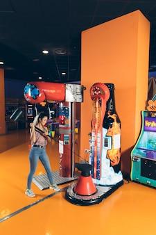 Zijdelings vrouw die arcadespel speelt