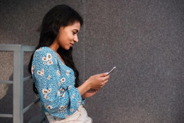 Zijdelings vrouw die een smartphone gebruikt