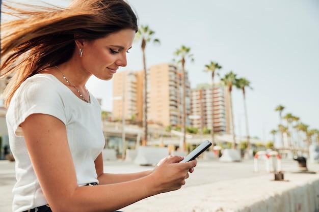 Zijdelings vrouw die haar telefoon bekijkt