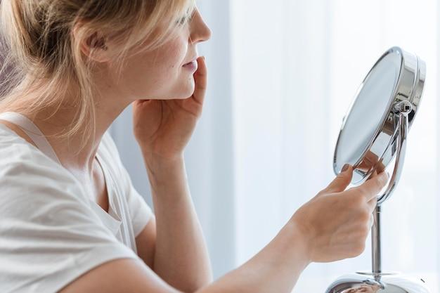 Zijdelings vrouw die in de spiegel kijkt