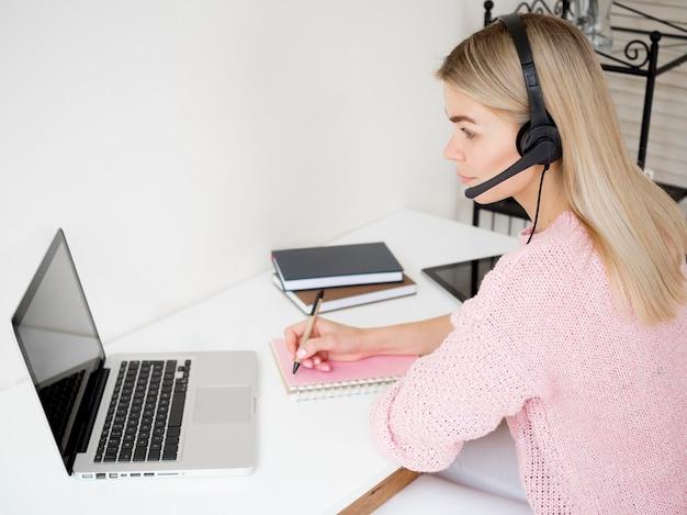 Zijdelings vrouw die online met hoofdtelefoons leert
