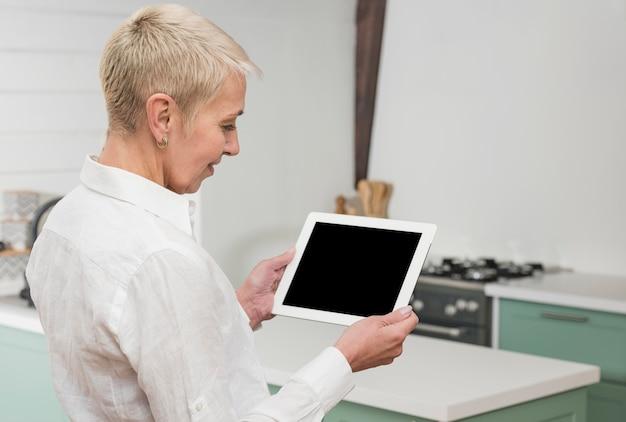 Zijdelings vrouw die op haar tablet kijkt
