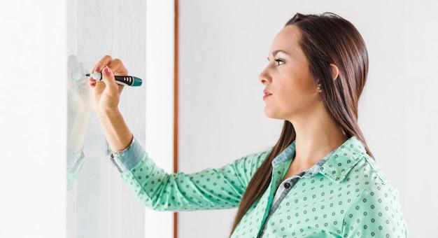 Zijdelings vrouw die op whiteboard schrijft