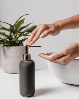 Zijdelings vrouw die vloeibare zeep gebruikt