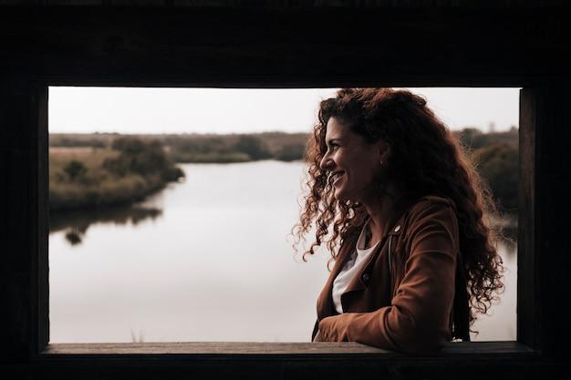 Zijdelings vrouw leunend tegen een raamlijst