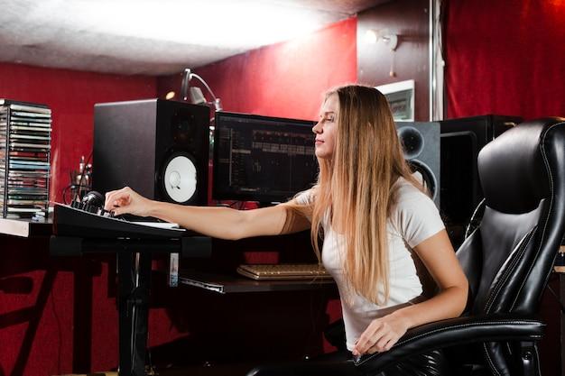 Zijdelings vrouwenzitting in een studio en het bekijken hoofdtelefoons