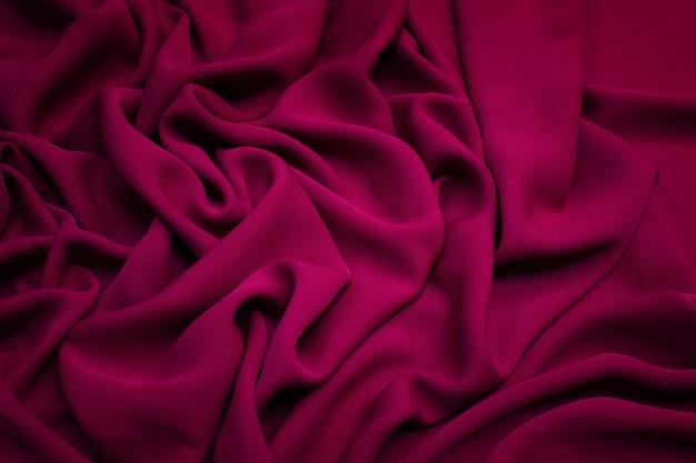 Zijden stof de kleur is karmozijnrood textuurachtergrond