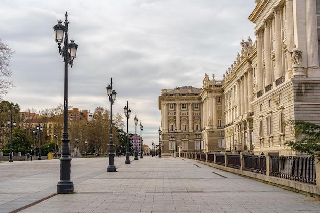 Zijgevel van het koninklijk paleis van madrid, voetgangersstraat met lantaarnpalen, bomen en zonnige dag met wolken. spanje.