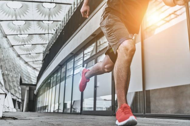 Zijn beste snelheid. close up van jonge man in sportkleding running