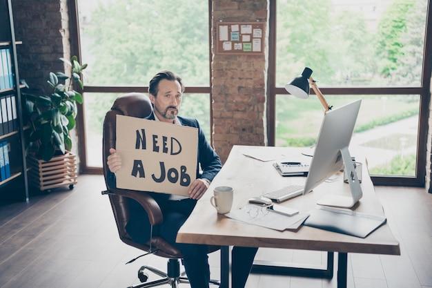 Zijn hij ontslagen agent makelaar financiën verzekering investeerder econoom web specialist deskundige man in handen plakkaat te houden zoeken nieuwe baan bij moderne loft baksteen industriële werkplek werkstation