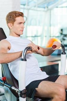 Zijn lichaam in perfecte vorm houden. geconcentreerde jonge man aan het trainen in de sportschool