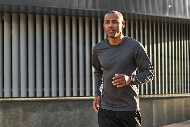Zijn lichaam sterk close-upportret maken van een jonge afrikaanse man in sportkleding die in de?