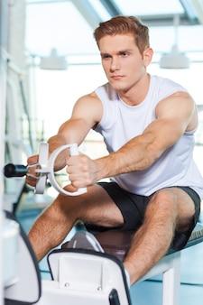 Zijn lichaam tot in de perfectie trainen. geconcentreerde jonge man aan het trainen in de sportschool