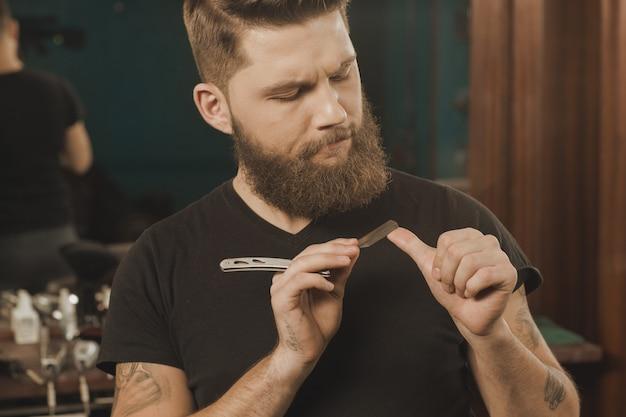 Zijn professionele tools. professionele kapper die zijn scheermes controleren die ernstig kijken