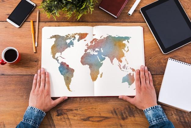 Zijn reis plannen. bovenaanzicht close-up beeld van man die handen vasthoudt op zijn notitieboekje met kleurrijke kaart erop terwijl hij aan het houten bureau zit