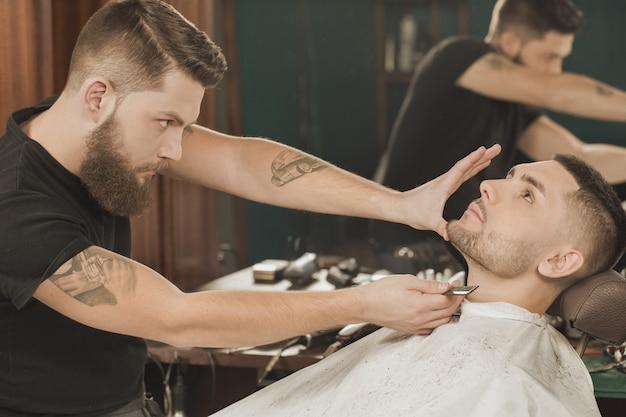 Zijn werk controleren. professionele kapper die zijn baardbesnoeiing controleert die aan de cliënt wordt gegeven