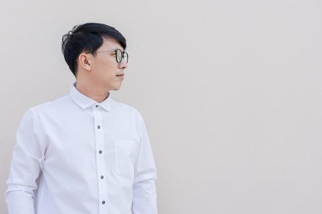 Zijportret van aziatische kerel in wit overhemd op muur.