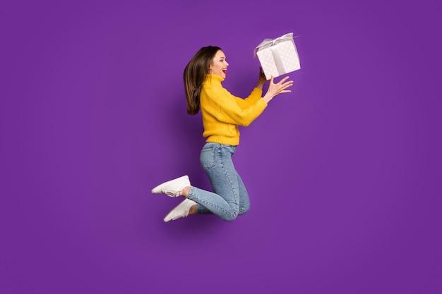 Zijportret van de lichaamsgrootte van de profiel volledige lengte van vrolijke dolblij positieve vrouw die giftbox vangen die omhoog springt.