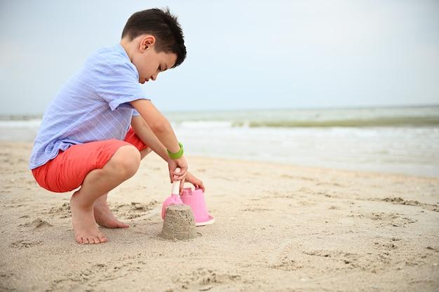 Zijportret van een gelukkige peuter die zandkastelen bouwt op het strand zomervakantie vac
