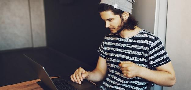 Zijportret van een jonge knappe man die thuis werkt op een laptop. panoramische bannerweergave.