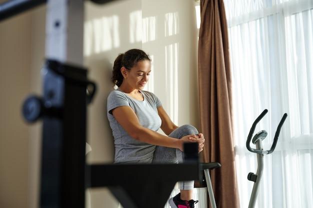 Zijportret van een jonge sportieve donkerbruine vrouw die haar rug tegen een muur rust en de spieren uitrekt
