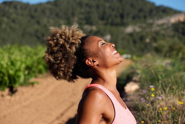 Zijportret van het gezonde jonge afrikaanse vrouw lachen in openlucht in ochtend