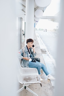 Zijportret van lachende man op mobiel telefoongesprek bij de bushalte op de luchthaven