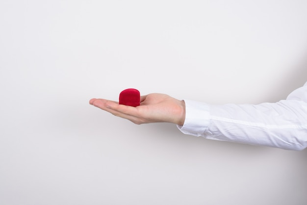 Zijprofiel close-up bijgesneden foto van hand met gesloten rood hartvormig klein doosje met ring binnen geïsoleerde grijze achtergrond