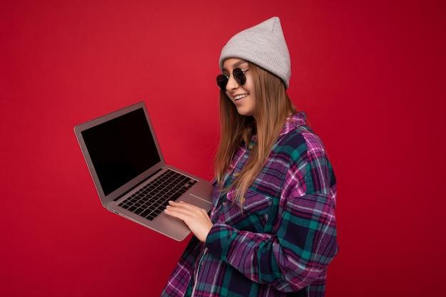 Zijprofiel mooie jonge vrouw met computer die casual slimme kleding zonnebrillen en hoed draagt