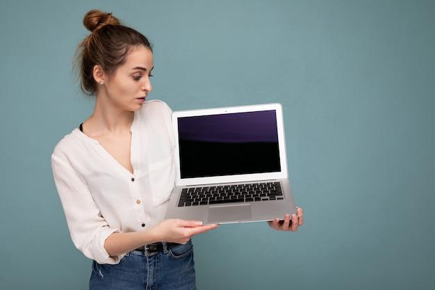 Zijprofiel portret van mooie glimlachende jonge vrouw met netbookcomputer